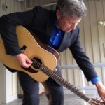 Eric Gibson tunes his new Henderson guitar.